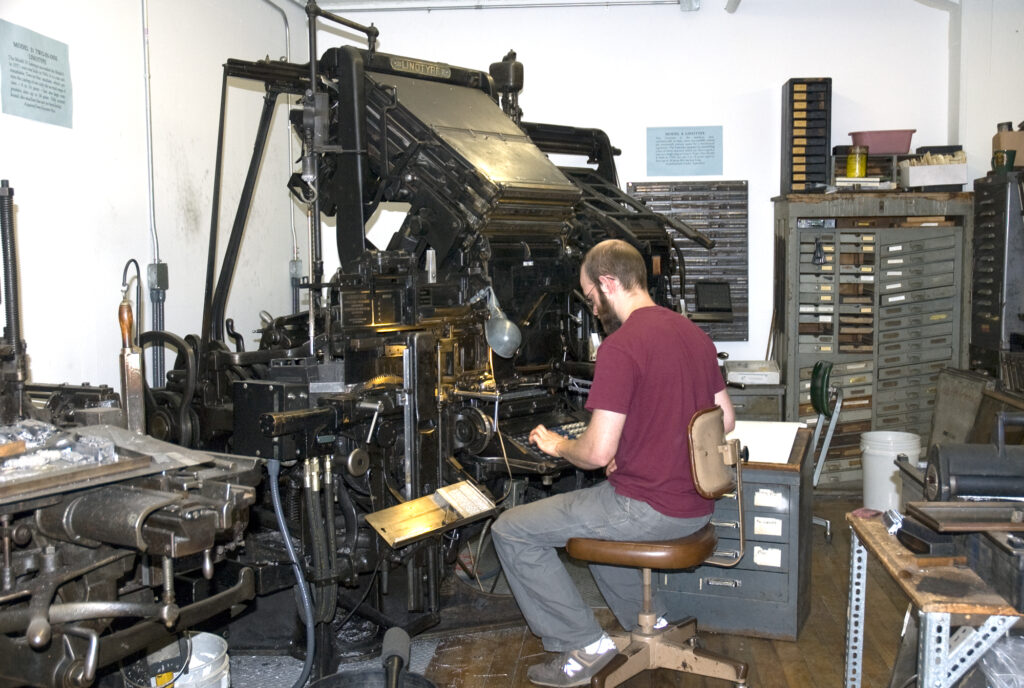 Jesse Marsolais working at the Linotype during his apprenticeship to John Kristensen.