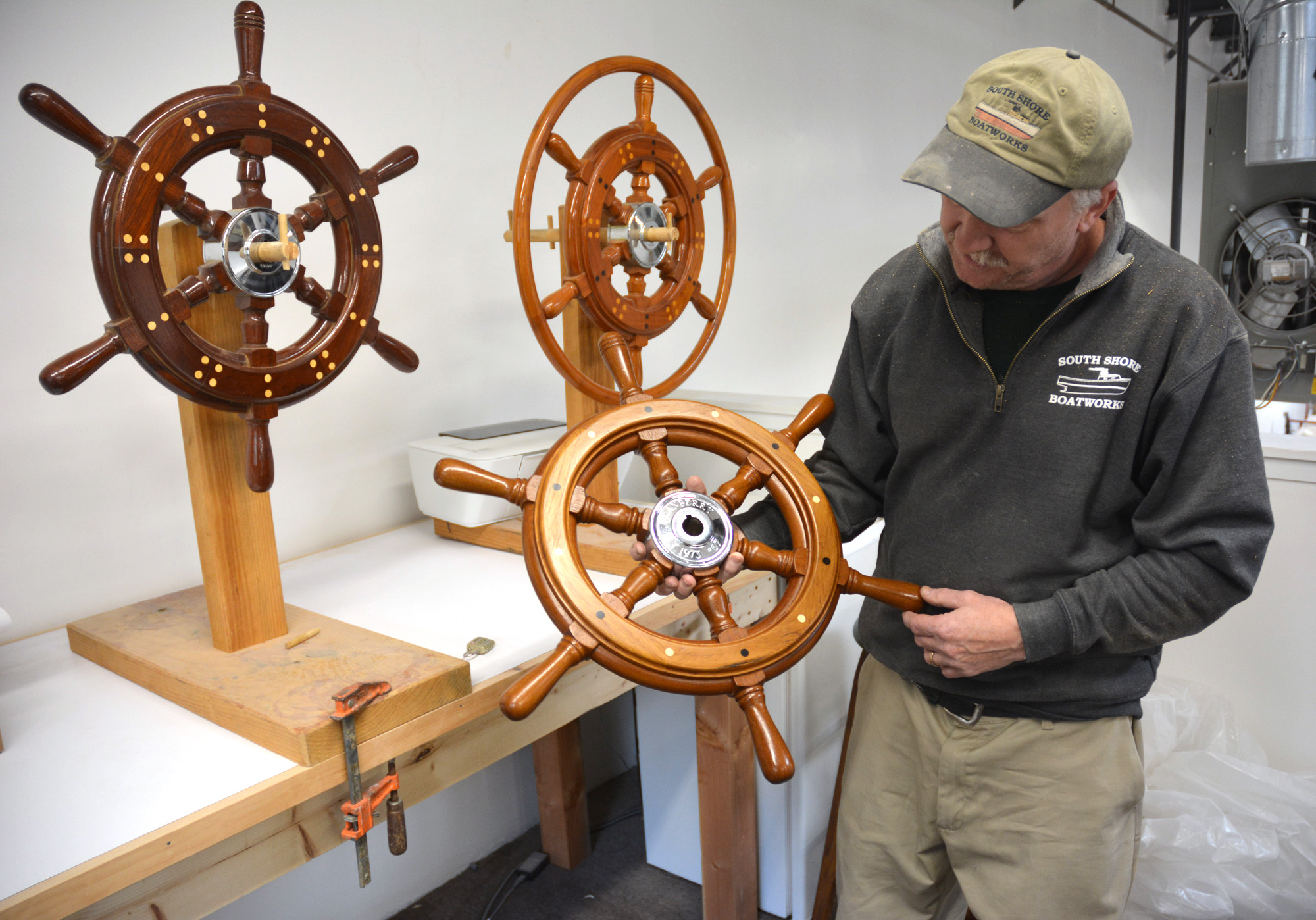 Bob Fuller holding one of his ship's wheels.