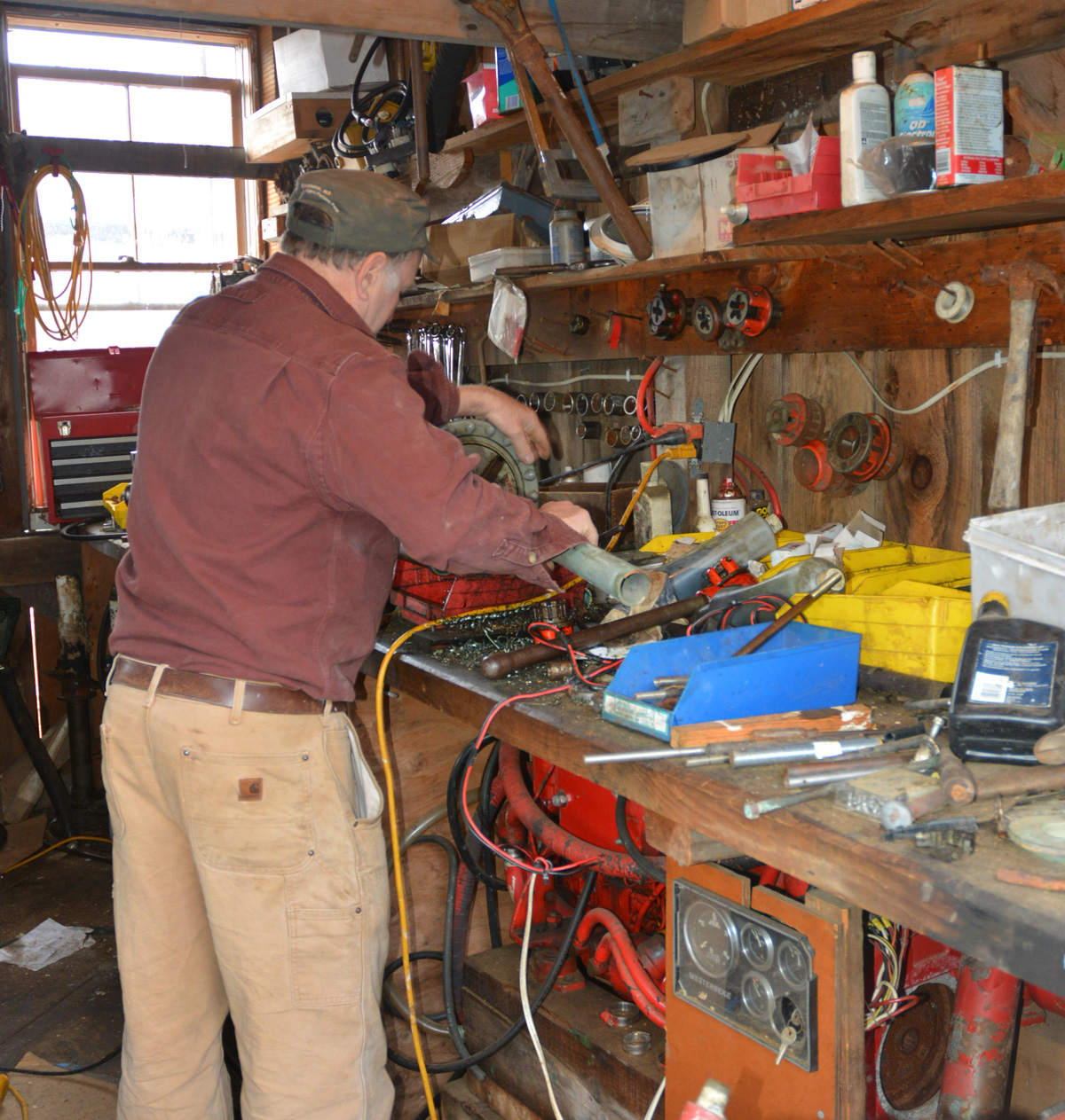Harold using a threading machine on a piece of pipe.