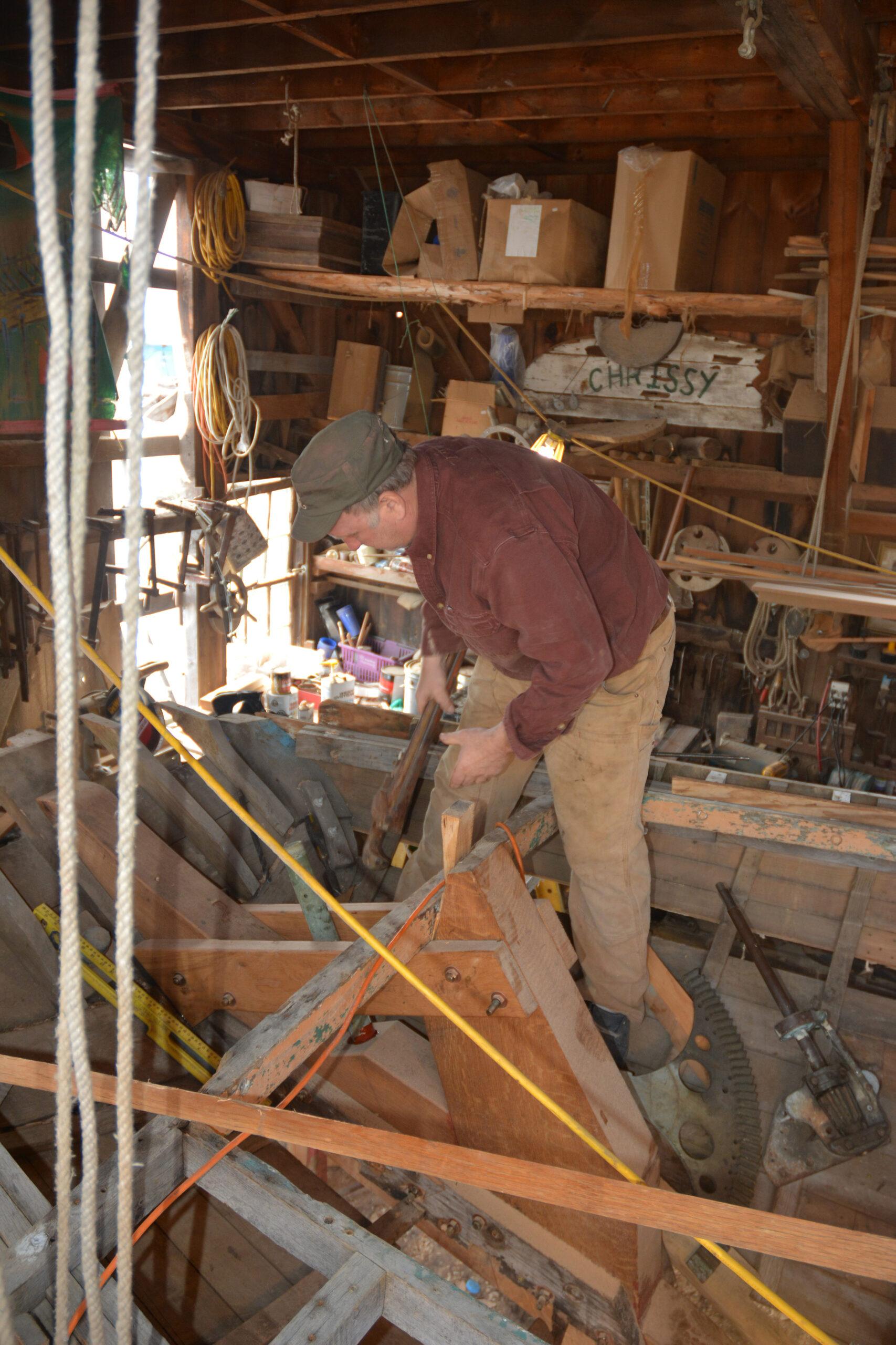 Harold climbing inside Maria carrying a wrench.