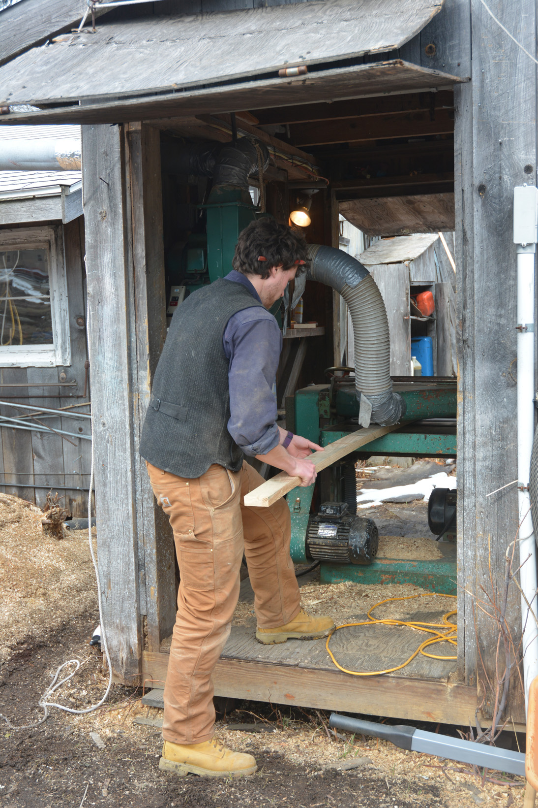 Alden feeing a plank into the planer.