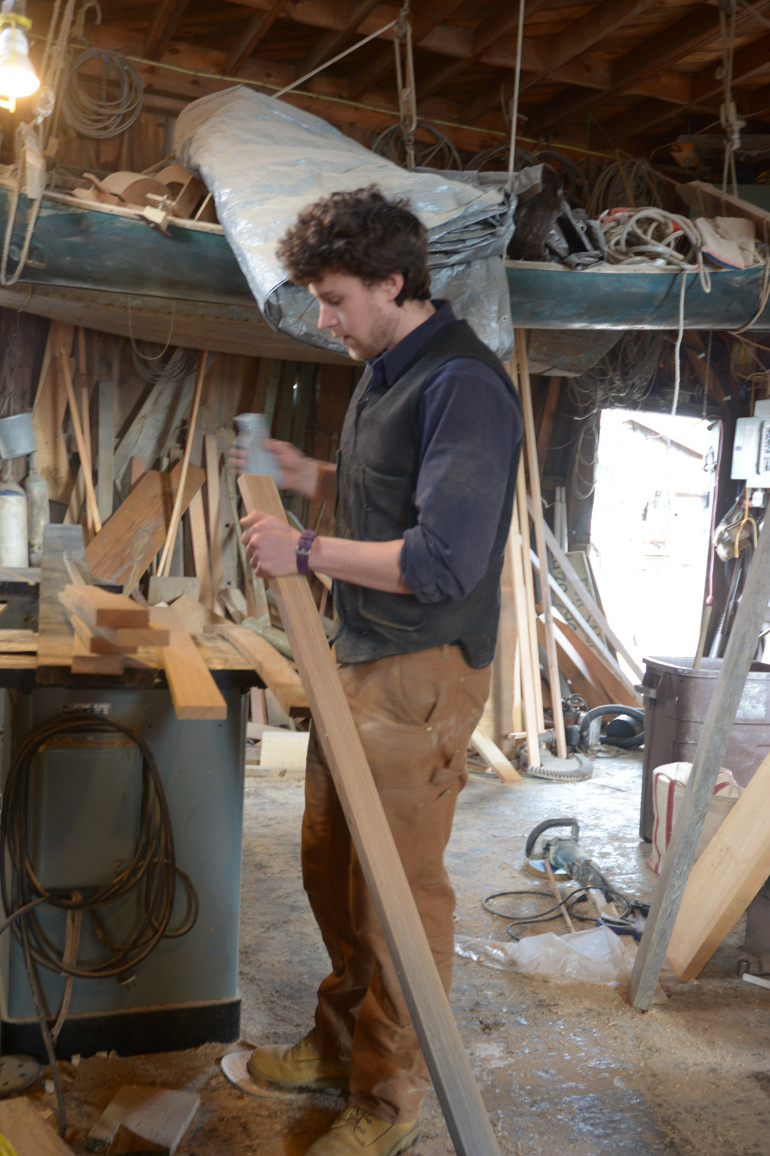 Alden sanding the end of a board that will become a rib.