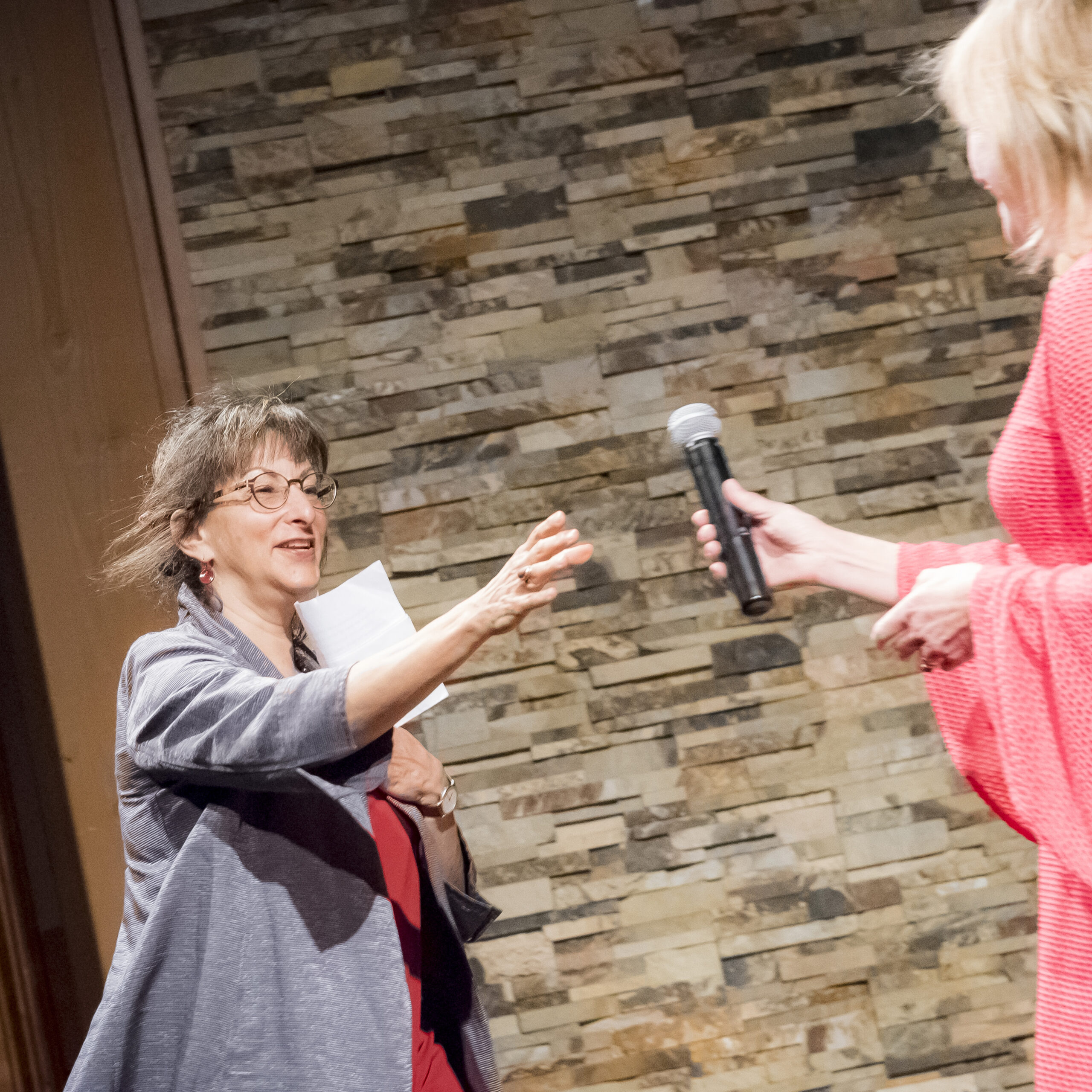 Anita Walker handing the microphone to Maggie Holtzberg.