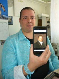 Jonathan James-Perry holding up a portrait of his ancestor, whale man Henry Gray James.
