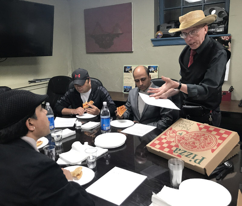 Group sitting around conference room table eating pizza.