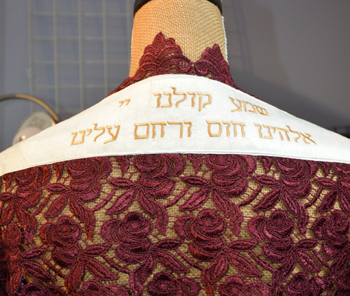 """Detail of embroidered attarah saying, """"Hear our voices"""" on tallit by Amy Lassman."""