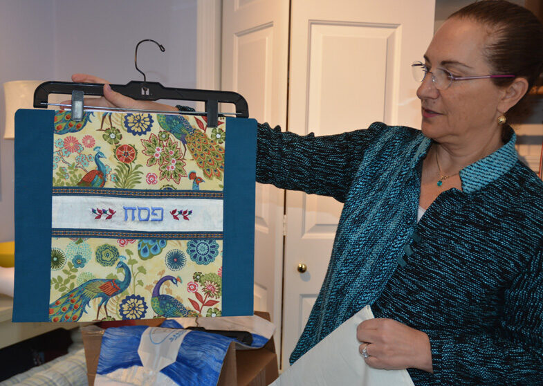 Amy holding up afikomen bag embroidered with Hebrew letters for Pesach.