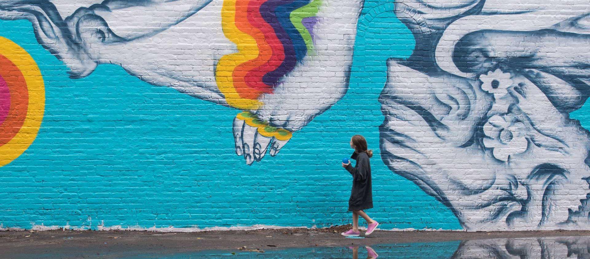 Girl looks at a mural at Beyond Walls Mural Festival, Lynn, MA