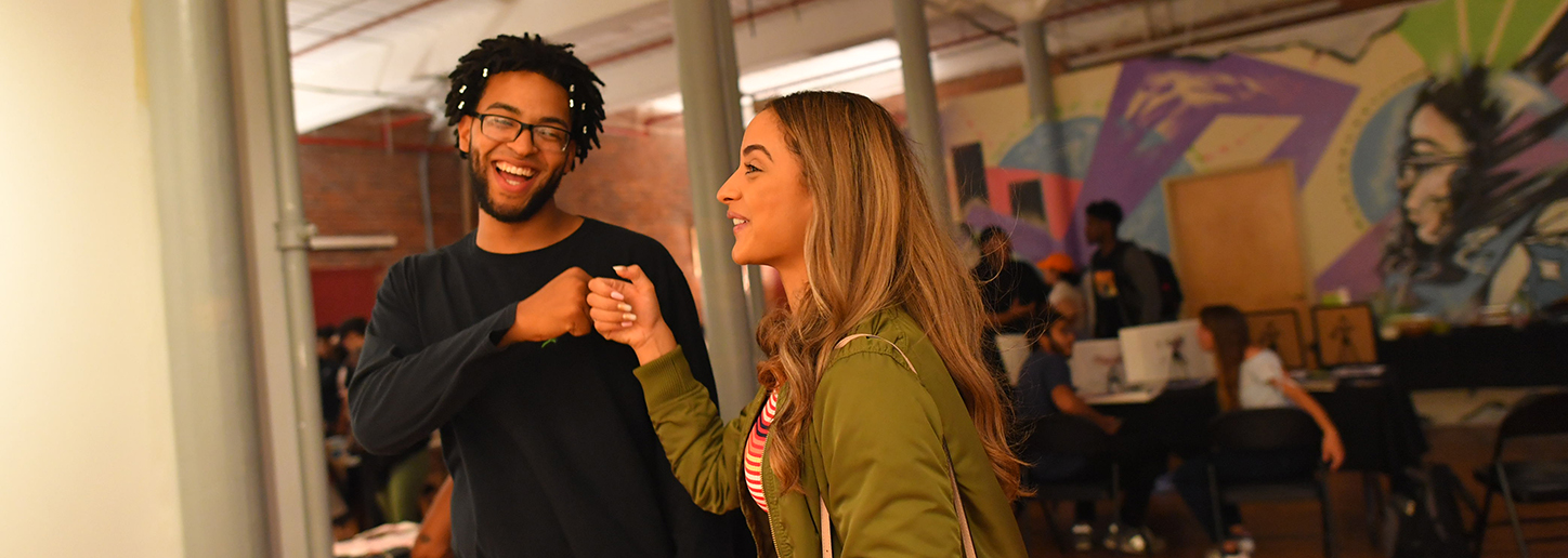Two young people smiling and fist-bumping in Elevated Thought gallery