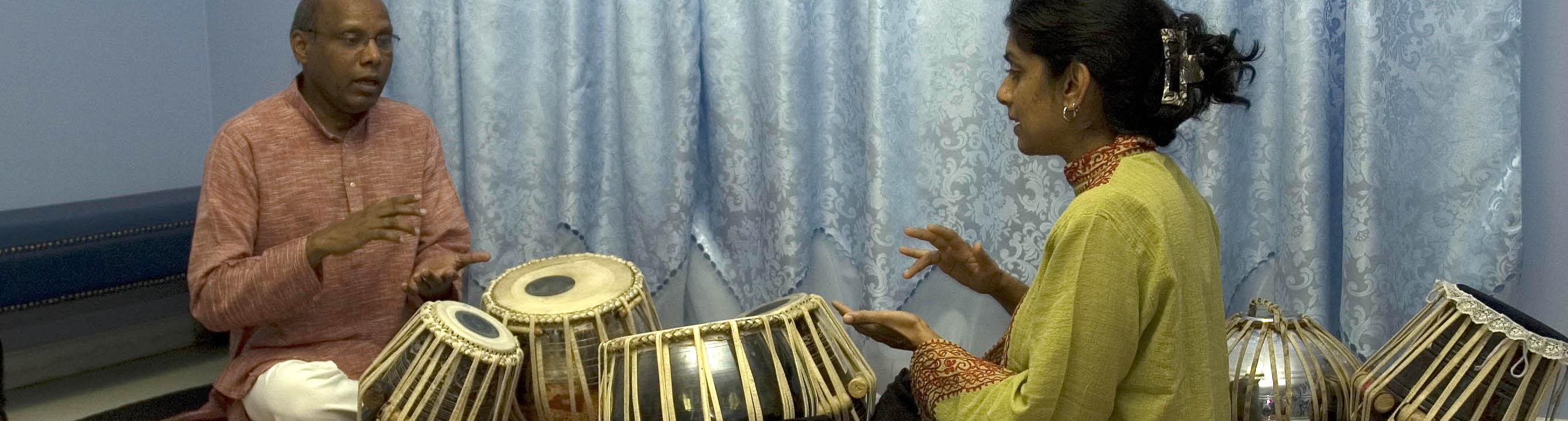 Chris Pereji playing tabla drums with apprentice Nisha Purushotham. Photo by Maggie Holtzberg.