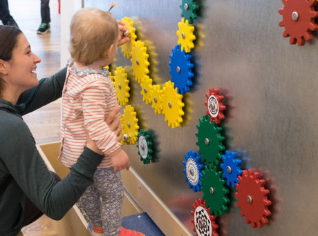 Women holds toddler up to a wall of colorful gears at the Discovery Museum in Acton.
