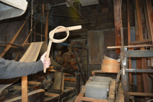 Jay holding a strip of oak that has been steamed and tied in a knot