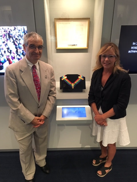 Steven M. Rothstein, Executive Director of the John F. Kennedy Library Foundation, with Anita Walker in the Legacy Room of the JFK Museum. Between them is the the federal legislation establishing the National Endowment for the Arts. Below that is Yo Yo Ma's Medal of Freedom. The Medal of Freedom was established by JFK to recognize the achievements of people in the arts, sciences, and other fields of endeavor beyond military achievement.