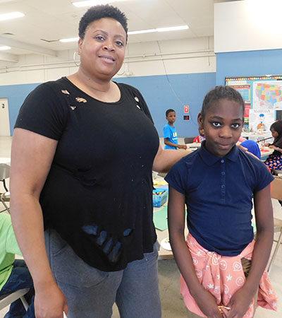 Tina Burston, head coordinator of the after-school program at Riverview Apartments, with Ja'Neyah Carroll, 11.