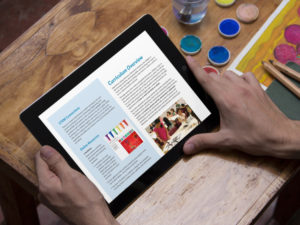 A person using a computer tablet to read the Creative Minds Out of School Time web site