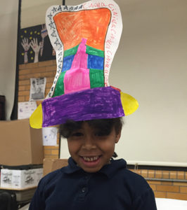 Smiling girl wearing a hat she made as part of a Creative Minds Out of School Time project.