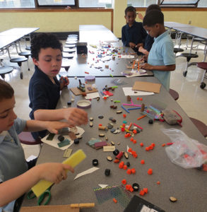 Boys assembling an artwork as part of a Creative Minds Out of School Time project.