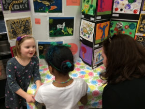 Girls standing in front of their artworks at a Creative Minds Out of School Time exhibition.