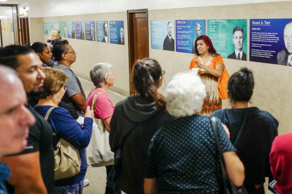 Michelle Guzman conducting tours of the hallway art guides a crowd through Mayors Row on the 3rd floor.