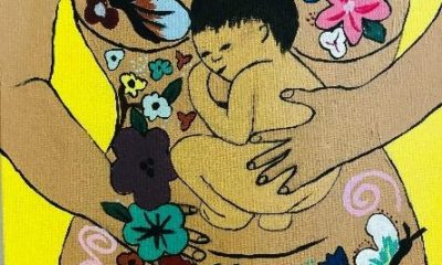 Painting of a woman's torso covered in flowers, her arms holding an infant lying on her belly.