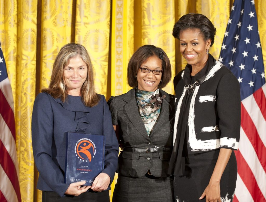 First Lady Michelle Obama awarding the President's Committee on the Arts and the Humanities to representatives from The Care Center.