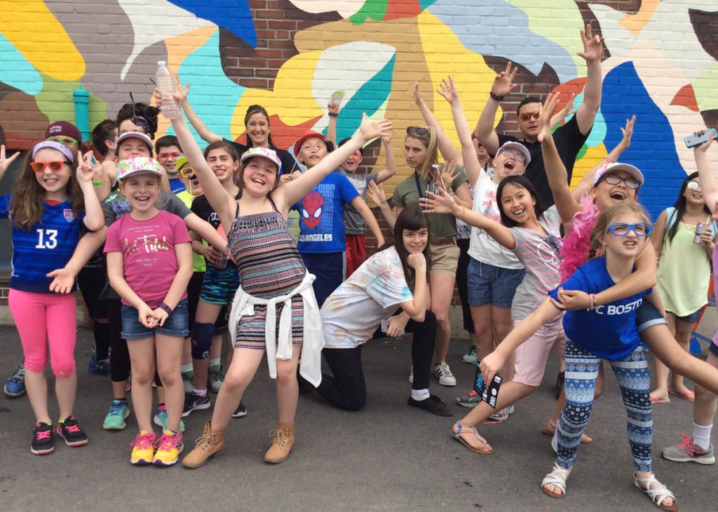 Group of young students smiling and proudly gesturing in front of a mural they helped create.
