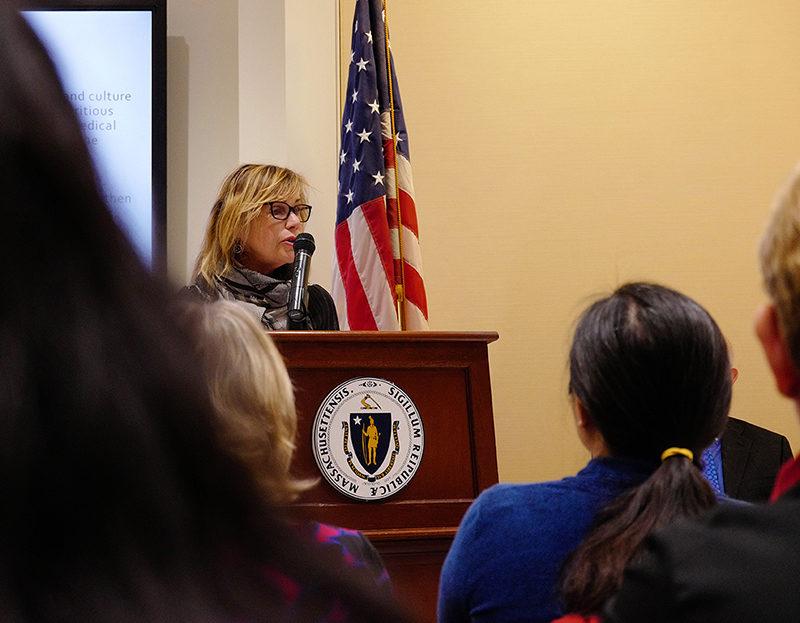 Anita Walker speaking at a podium at the State House