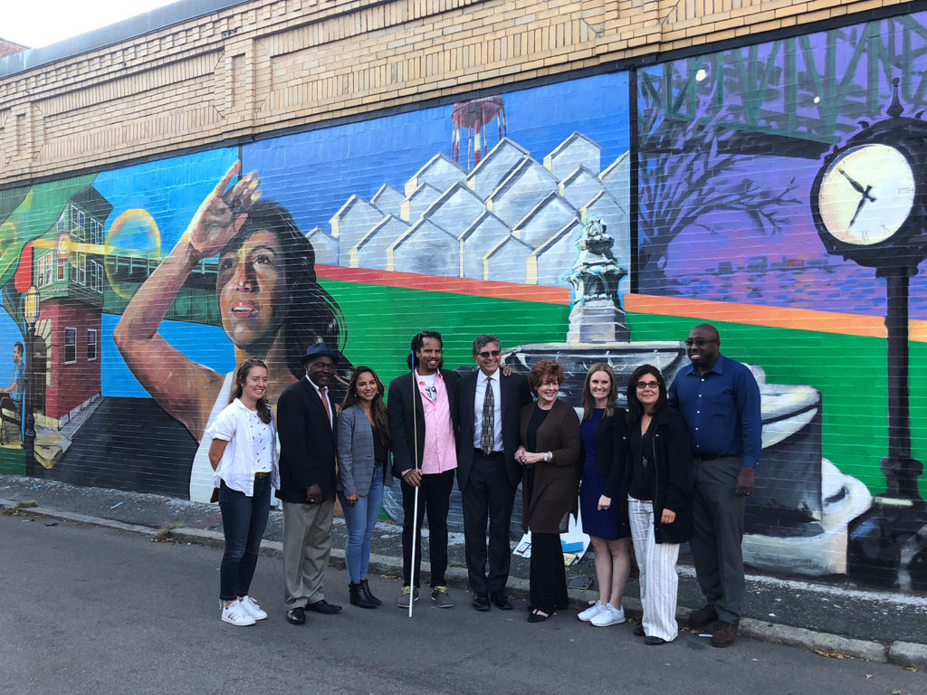 """Community members stand in front of the """"Chelsea Right Now"""" mural painted by Demetrius Fuller."""