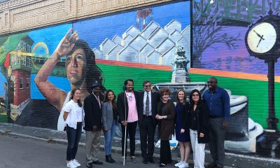 Community members stand in front of a mural