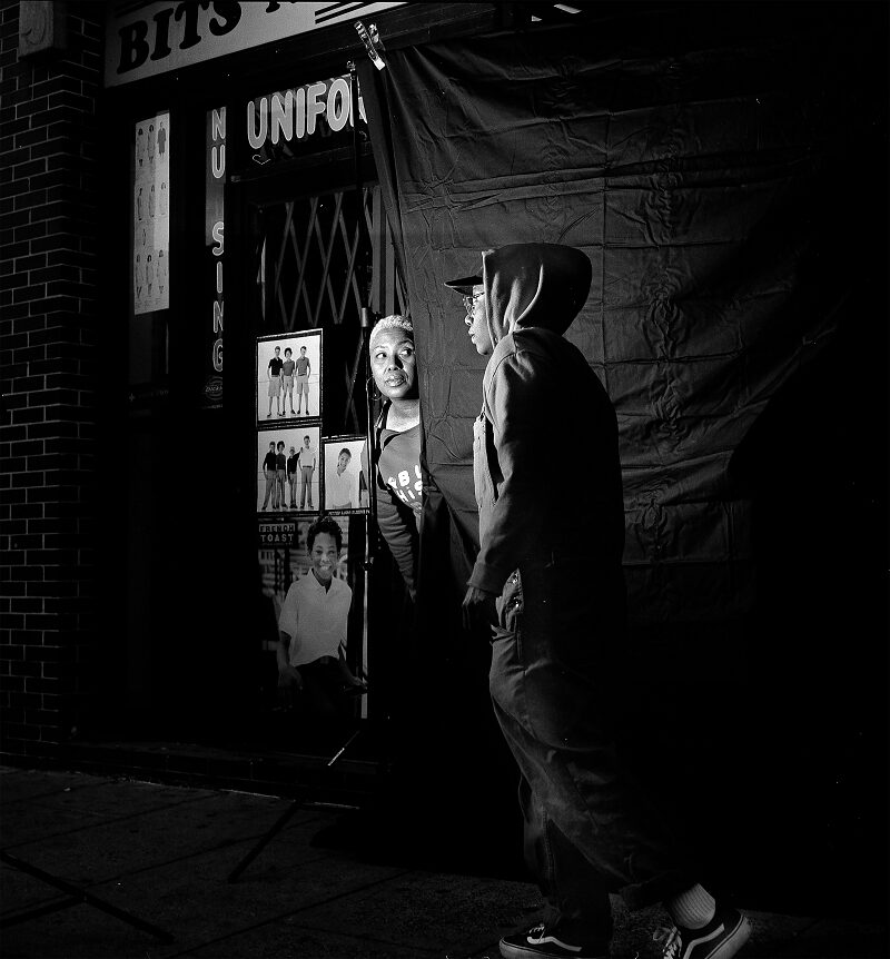 City at night, two people under spotlight glare, a woman peers out from behind a curtain, a young man walking by her.