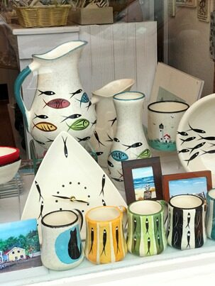 Pottery pieces with fish decorations in shop window.