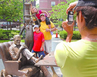 Family taking photos on a Dr. Suess sculpture in the quadrangle at the Springfield Museums