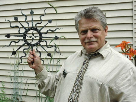 Jonas holding a saule with imagery of the sun, snakes, and thunderbolts.
