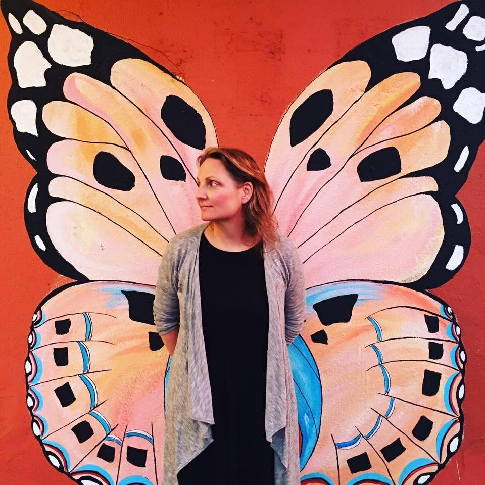 Sienna Wildfield in front of a butterfly mural.