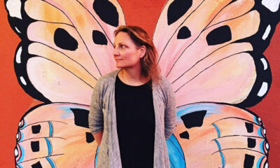 Sienna Wildfield in front of a Butterfly mural