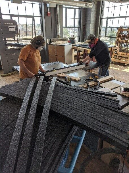 Technocopia members prepare to cut PPE wood shop foam.