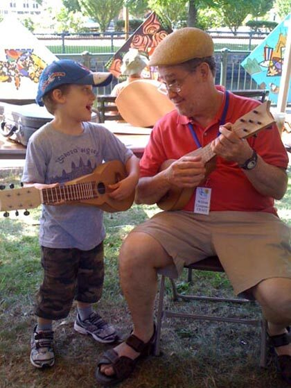William Cumpiano playing cuatro with young festival-goer, 2011.