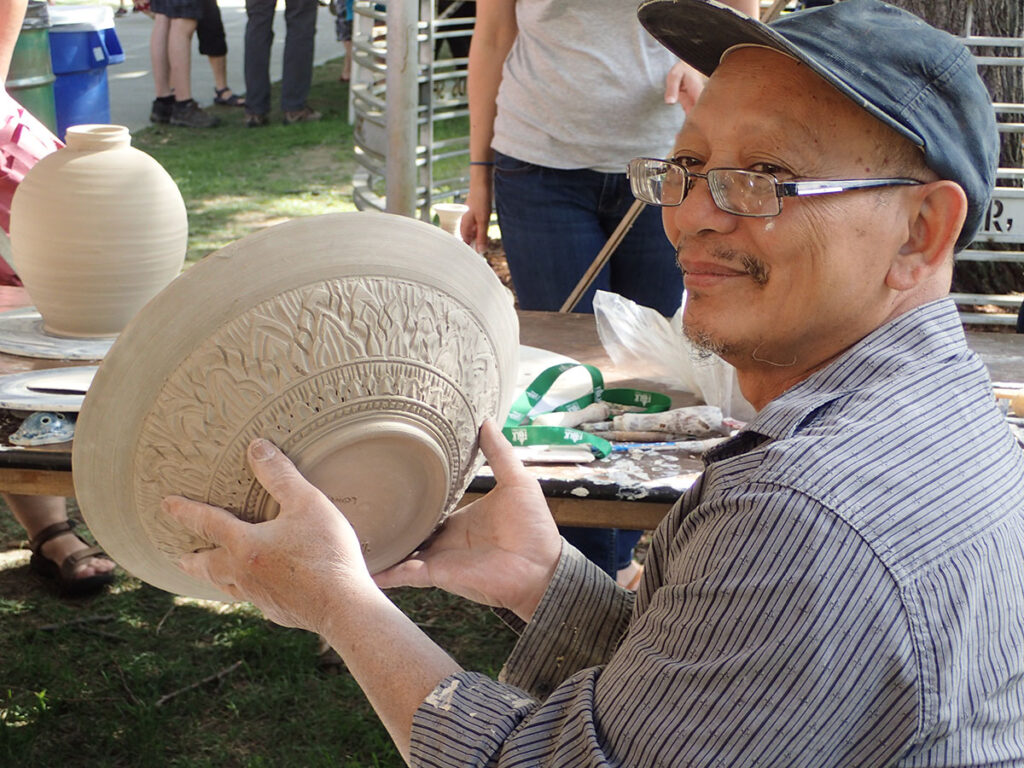 Yary Livan holding up an unglazed bowl, 2018.