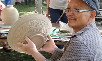 Yary Livan holding up an unglazed bowl, 2018.