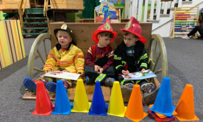 Three children dressed as firefighters play at Cape Cod Children's Museum.