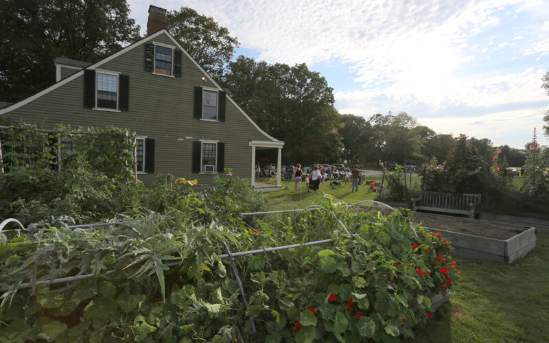 Gardens and people gathered on front lawn of the 1835 Farm Manager's Cottage at Gore Place Society