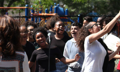 A small group of youth artists singing and smiling during an outdoor performance
