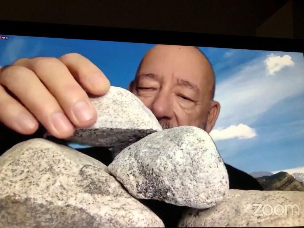 Close up of a bald man stacking rocks