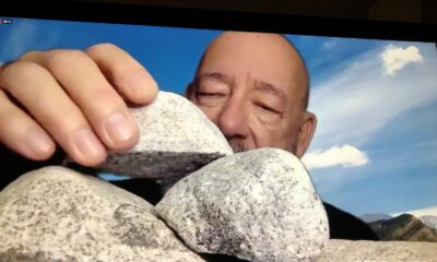 Close up of a bald man stacking rocks