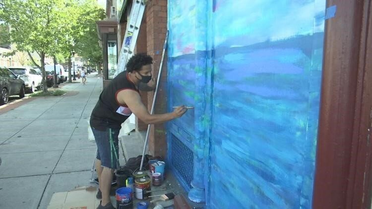Man with dark, curly hair wears a mask while painting a mural