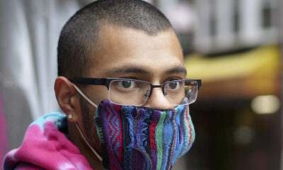 Young man with a buzz cut, glasses, a colorful face mask, wearing a tie-dyed hoodie