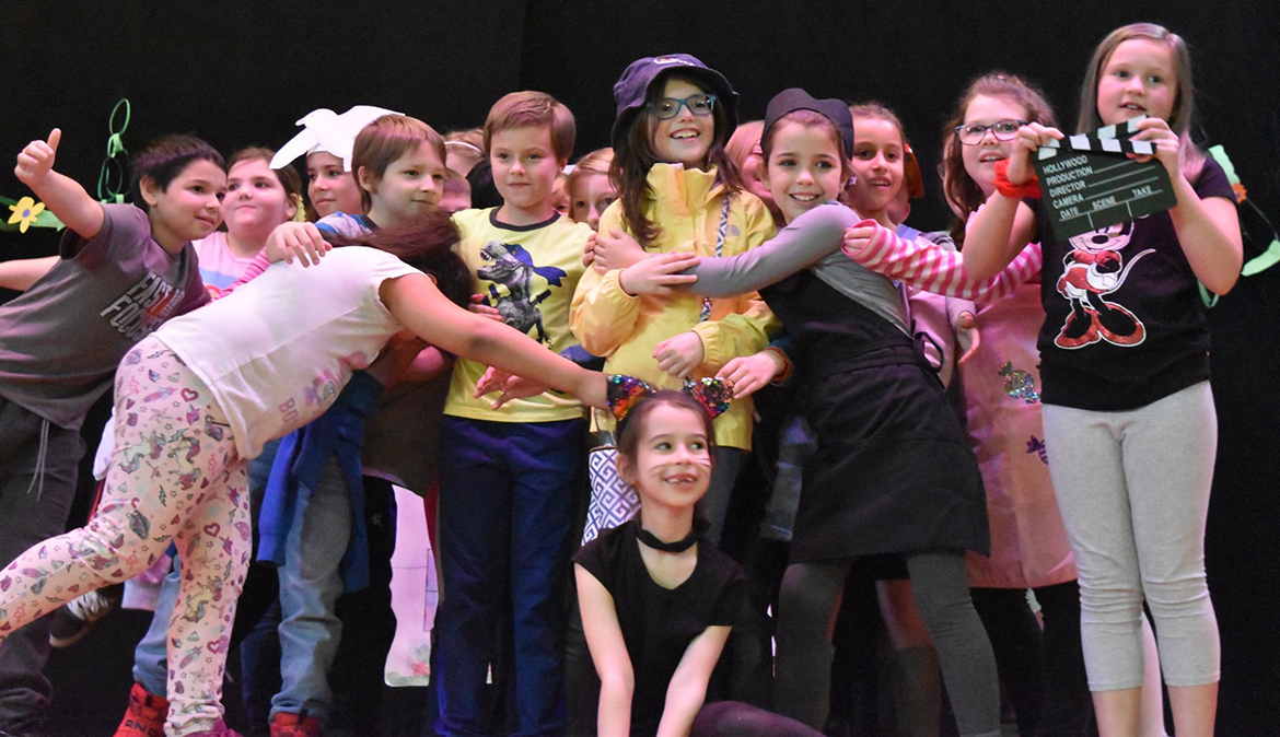 Children smiling on a stage with Enchanted Circle Theater