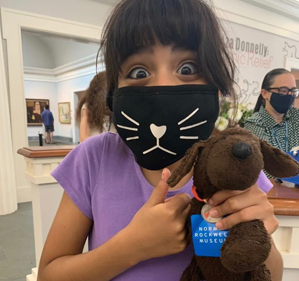 Girl wearing mask with happy eyes and a thumbs up and stuffed animal at the Norman Rockwell Museum.