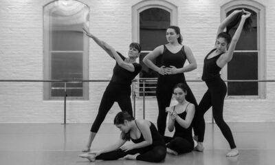 Five dancers in black leotards