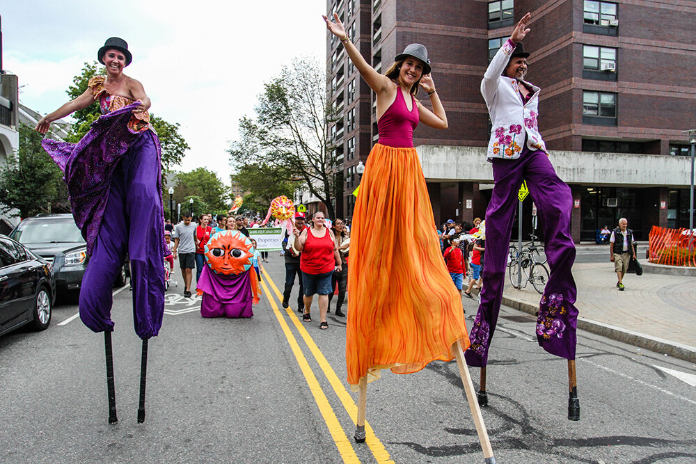 three people walk on stilts, wearing bright, flowing pants as part of IBA's Festival Betances